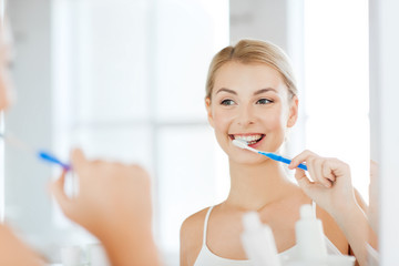 woman with toothbrush cleaning teeth at bathroom