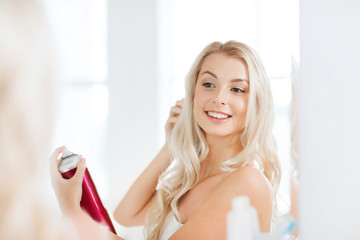 woman with hairspray styling her hair at bathroom