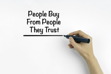 Hand with marker writing: People Buy From People They Trust