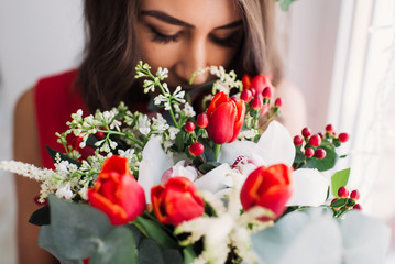 beautiful young girl in a red dress at a window with a wreath on his head and a bouquet of flowers, enjoying the smell of flowers