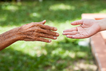 The old man hand and a young woman hand