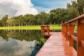 Pier or dock into lake pond with trees field grass and storm clouds on horizon and in reflection looking serene peaceful relaxing rural isolated secluded