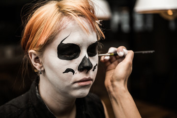 Professional make up artist applying halloween face paint