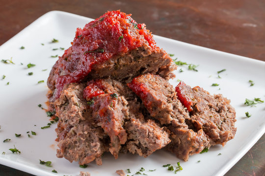 Sliced freshly cooked traditional meatloaf with ketchup tomato sauce isolated on white plate