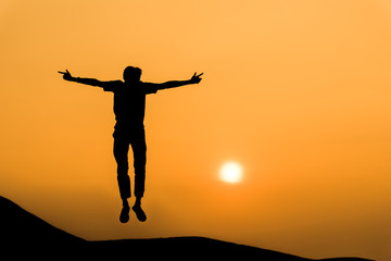 Silhouette of man in happy jump on orange sunset sky