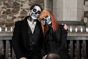 Evil day of the dead undead couple sitting on bench in cemetery