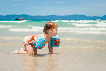 Little girl in armbands crawls to something in the sea. South China sea, Vietnam.