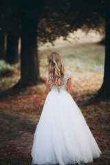 Luxuty portrait of blonde bride with bridal bouquet in autumn