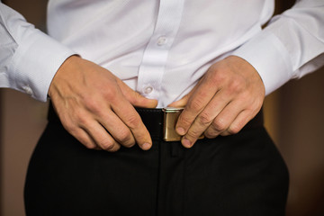 man corrects belt, fees groom, man's hands, dressing, man wear pants, jeans, man's style