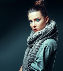 Fashion brunette model in nice clothes posing in the studio with makeup and hairstyle.