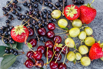 Mix of fresh and juicy cherries, black currant, strawberries and gooseberries in the summer garden on a grey stone