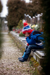 Sad little boy, sitting on a grave in a cemetery