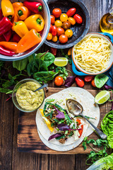 Making traditional mexican fajitas or tortillas on wooden table,
