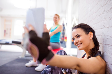 Fit woman in gym holding smart phone, taking selfie