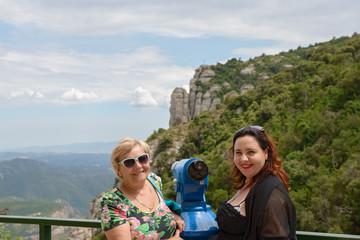 Women are beside telescope in Montserrat Abbey on mountain backg