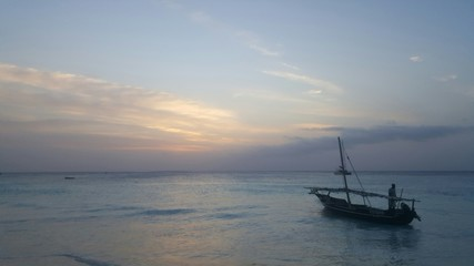 Traditional Dhow boat floating in the ocean as they he sun sets in Nungwi, Zanzibar