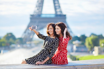 Beautiful twin sisters taking selfie in front of Eiffel Tower