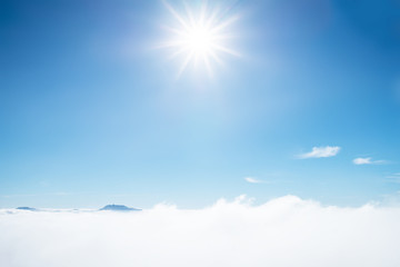 Sun rays shinning in the blue sky. Blue sky with layer of white hazy clouds.
