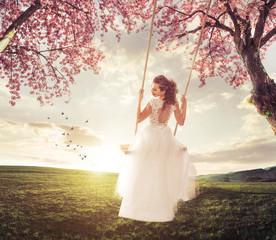 Beautiful Bride swing in the spring meadow