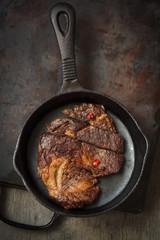 Beef ribeye bone-in steak cut in a frying pan,selective focus