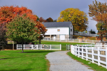 Lancaster, Pennslvania - October 18, 2015:  White fences, pathways, trees with Autumn foliage, and the Old Farm Equipment Shed at the Amish Farm and House *