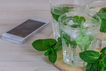 glass of cold water with fresh mint leaves and ice cubes on wood