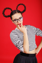 High fashion girl in the glasses with unusual hairstyle like Minnie Mouse in the studio