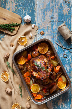 Christmas roasted chicken with crispy brown skin, stuffed with various vegetables and spices in baking dish in vintage wooden table background. Rustic style, top view.