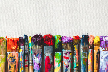 Row of artist paintbrushes closeup on artistic canvas. Wall mural