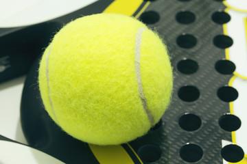 Paddle ball on racket. Yellow paddle ball laying on racket.