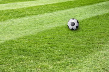 Conceptual soccer ball field background. Soccer ball waiting on sunny soccer field ground.