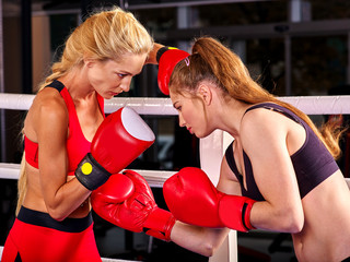Two  women boxer wearing red  gloves to box in ring. Aggressive training.