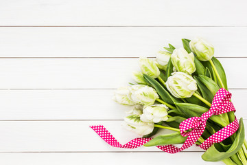 Bouquet of white tulips decorated with ribbon on white wooden background. Top view. copy space