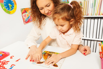 Little schoolgirl pieces together a jigsaw puzzle