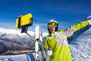 Happy screaming skier take photo with camera