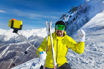 Happy skier man taking selfie on mountain