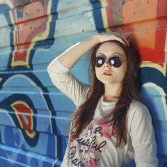 Stylish hipster girl in the sunglasses and jeans outdoor