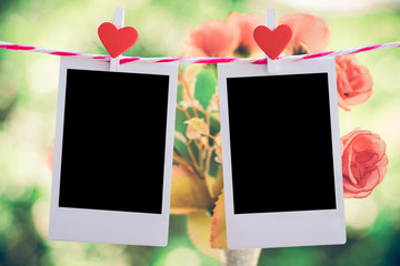 2 Blank instant photo and red clippaper heart hanging on the clothesline with pink rose flower background. vintage tone.Designer concept.