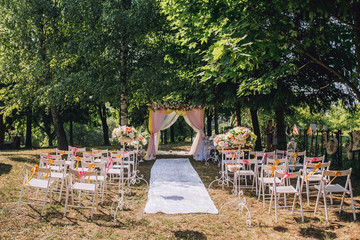arch for the wedding ceremony of burlap and wooden logs in pine forest with details