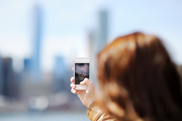 Female tourist taking mobile photo of skyscrapers