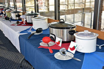 row of crock pots for a chili cook off in a restaurant