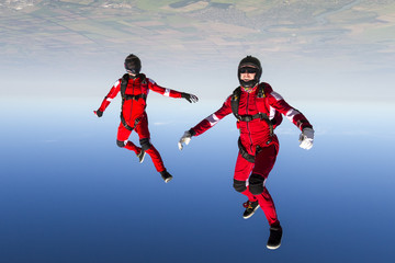 Two sports parachutist build a figure in free fall.