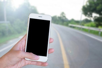 Hands woman are holding touch screen smart phone,tablet on blurred road nature background.