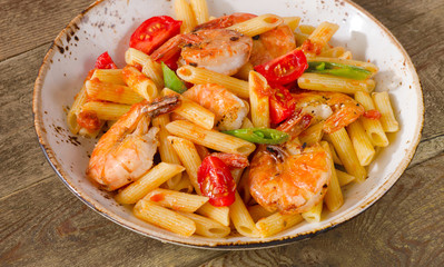 Penne pasta with shrimp and tomatoes  on a rustic wooden table.