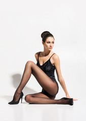 Gorgeous, seductive woman sitting in sexy pose wearing alluring hosiery and heels over isolated background.