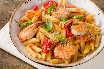 Penne pasta with shrimp, tomatoes and herbs on wooden table.