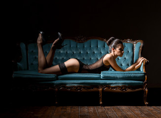 Young and sexy woman in lingerie on a vintage sofa