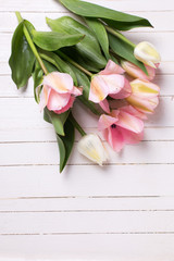 Bunch of fresh  spring  pink  tulips  on white  painted wooden b