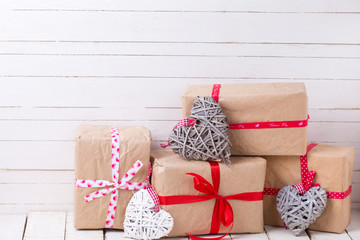 Festive gift boxes and  grey and whute decorative hearts  on white wooden background. Selective focus. Place for text..