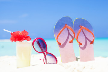 colourful picture of flip flops, pina colada cocktail with hibiscus and pink sunglasses near the beach